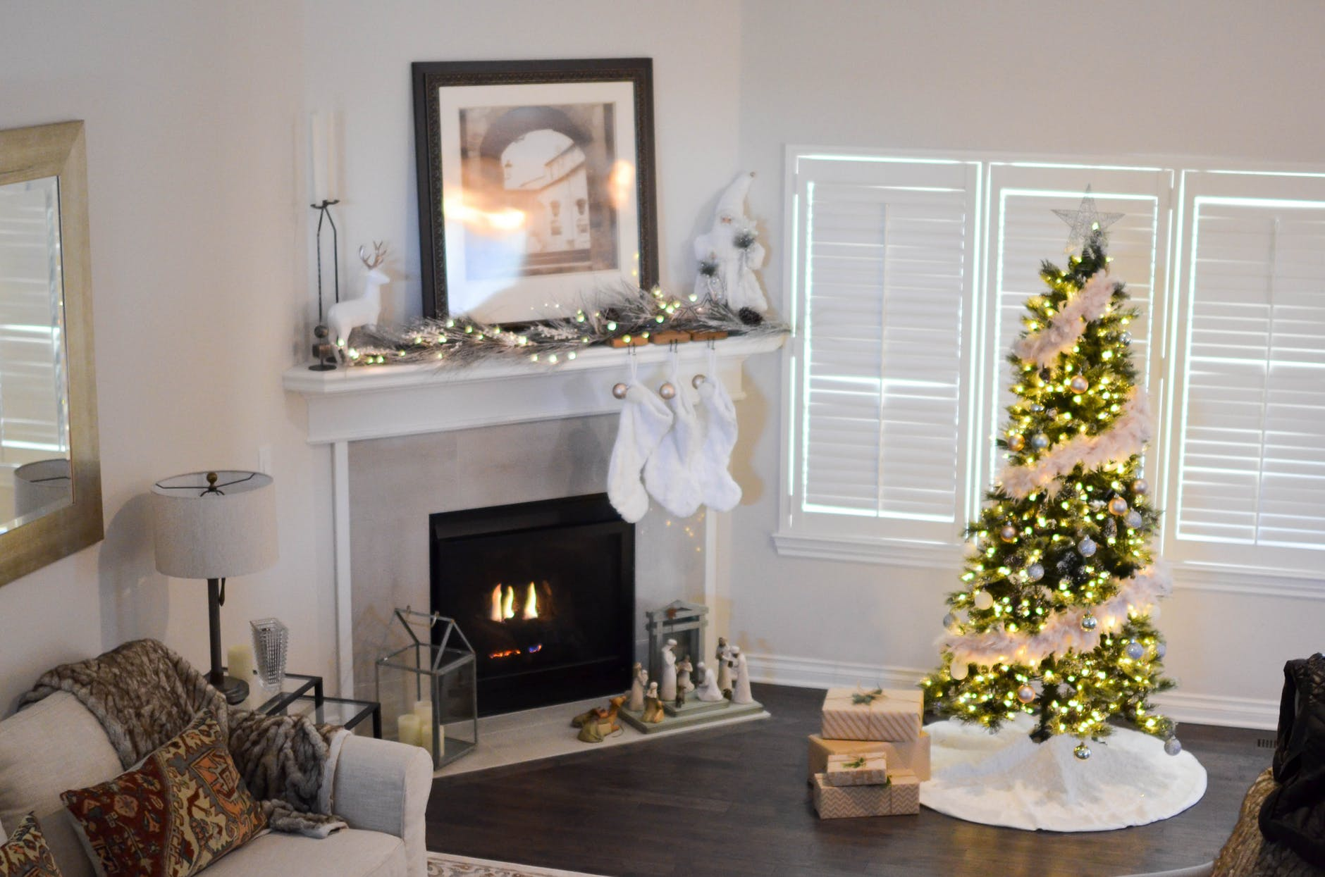 green and white pre lit pine tree near fireplace inside well lit room